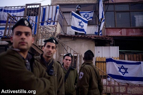 Israeli Border Police officers look on during a protest against the eviction of Palestinians from their homes by Israeli settlers in the East Jerusalem neighborhood of Sheikh Jarrah, December 25, 2009. (Oren Ziv/Activestills.org)