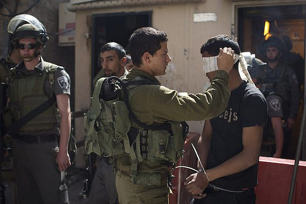 Israeli soldiers arrest a Palestinian in Hebron. File photo by Activestills.org