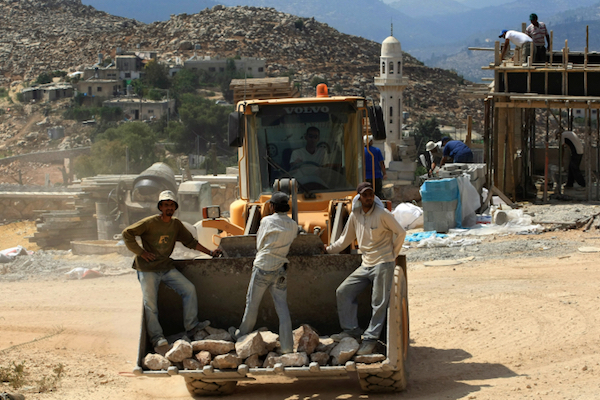 Palestinian construction workers build a new house  in the West Bank settlement of Har Gilo, on the outskirts of Jerusalem, Monday, Sept. 7, 2009. (Kobi Gideon/Flash90)