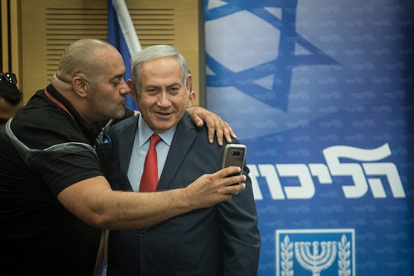 Prime Minister Benjamin Netanyahu poses for a selfie with a Likud activist during a party faction meeting in the Knesset, July 9, 2018. (Hadas Parush/Flash90)