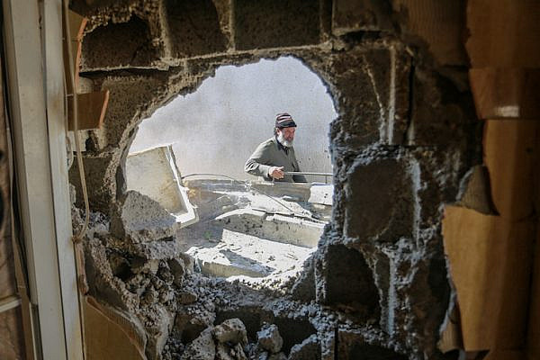 A Palestinian man checks the damage following an Israeli air strike in the southern Gaza Strip city of Khan Yunis, March 10, 2019. (Abed Rahim Khatib/Flash90)