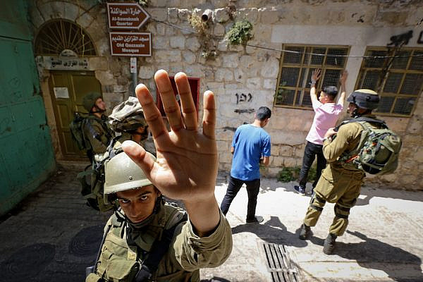 An Israeli soldier attempts to block the view of a photographer as soldiers body search Palestinian men in the West Bank city of Hebron on June 22, 2017. (Wisam Hashlamoun/Flash90)