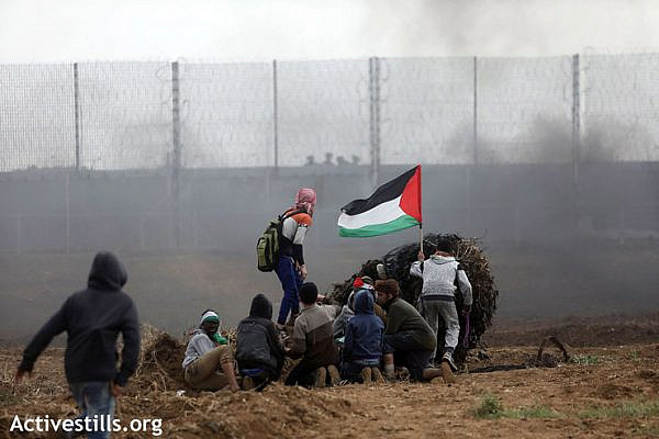 A group of protesters wave a Palestinian flag while trying to take cover during the demonstration, east of Gaza City, March 30, 2019. (Mohammed Zaanoun/Activestills.org)