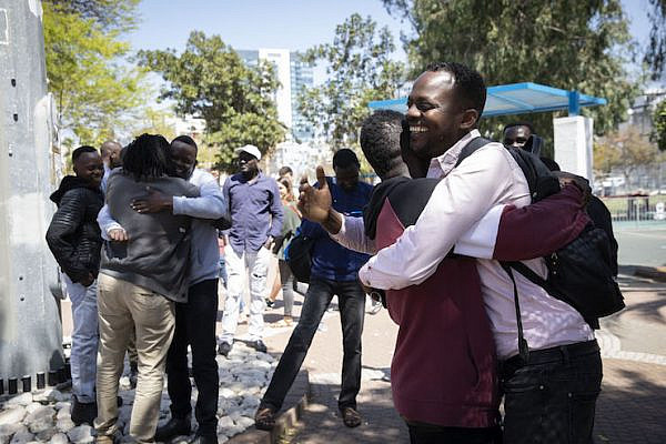 Sudanese asylum seekers embrace in south Tel Aviv's Levinksy Park following the announcement that Omar al-Bashir will step down after 30 years in power,  April 11, 2019. (Oren Ziv/Activestills.org)