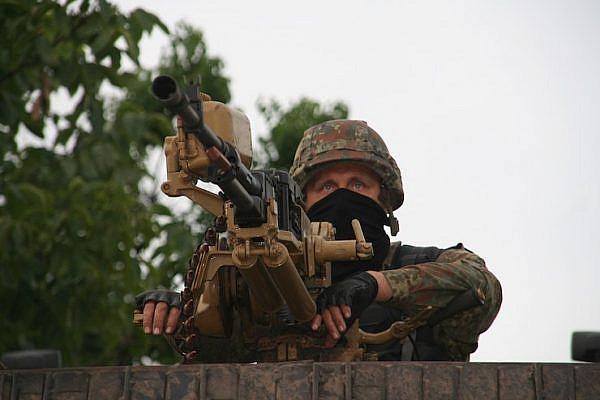 A soldier of the Azov Battalion mans a heavy machine gun on a patrol near Mariupol, Ukraine. (Carl Ridderstråle/CC BY-SA 4.0)