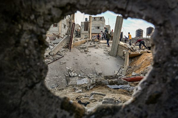 Palestinians walk through the wreckage of a building that was damaged by Israeli air strikes in Rafah in the southern Gaza Strip, on May 5, 2019. (Abed Rahim Khatib/Flash90)