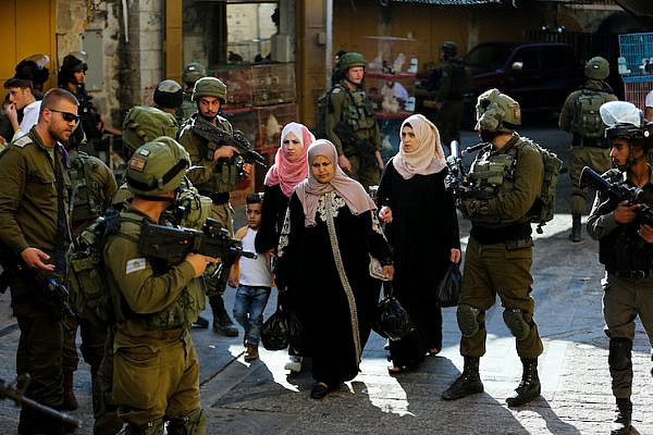 Israeli security forces guard as Jewish Israelis tour the Palestinian side of the old city market in the West Bank city of Hebron, June 15, 2019. (Wisam Hashlamoun/Flash90)