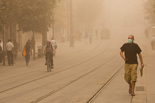 Israelis walk across the light rail tracks in Jerusalem, September 8, 2015, as a  sand storm hits Israel. (Yonatan Sindel/Flash90)