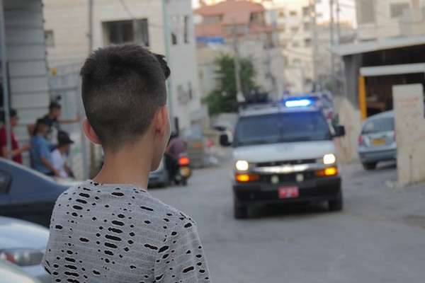 A Palestinian child looks on at a police vehicle in the East Jerusalem neighborhood of Issawiya. (Yuval Abraham)
