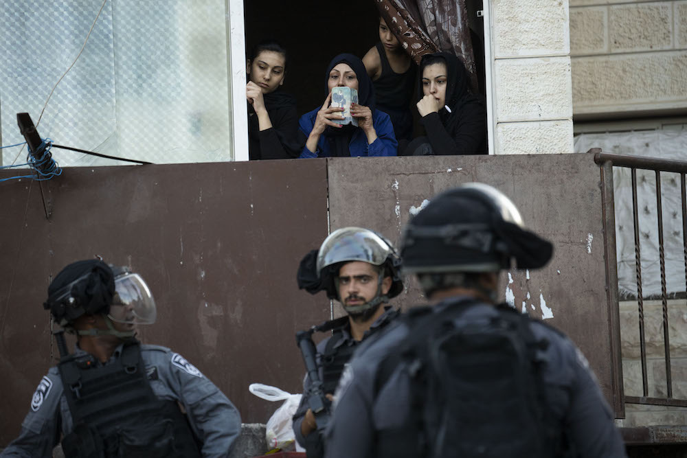 Palestinian women look on during a raid by Israeli police in the East Jerusalem neighborhood of Issawiya, July 1, 2019. (Oren Ziv/Activestills.org)