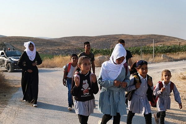 Students from the Palestinian village of A-Tuba in the South Hebron Hills walk to school as the Israeli army escorts them to protect them from settler violence. (Rachel Shor)