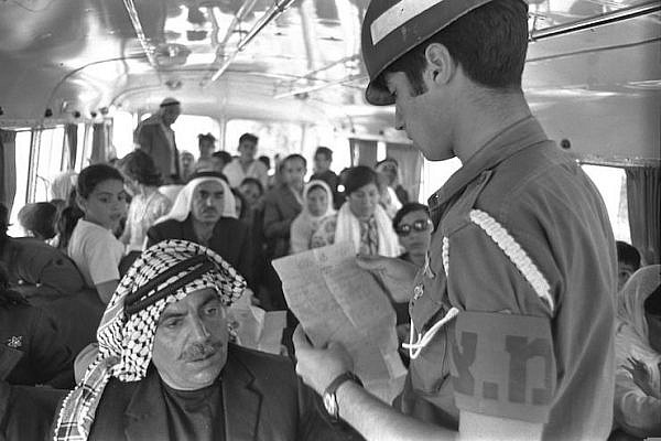 An Israeli military police officer checks entry permits of Palestinians on a bus crossing the Allenby Bridge into Israel. (Moshe Milner/GPO)