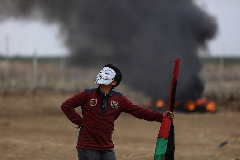 A young Palestinian protester wearing a Guy Fawkes mask holds a Palestinian flag and looks on during clashes with Israeli soldiers in eastern Gaza City, May 4, 2018. (Wissam Nassar/Flash90)