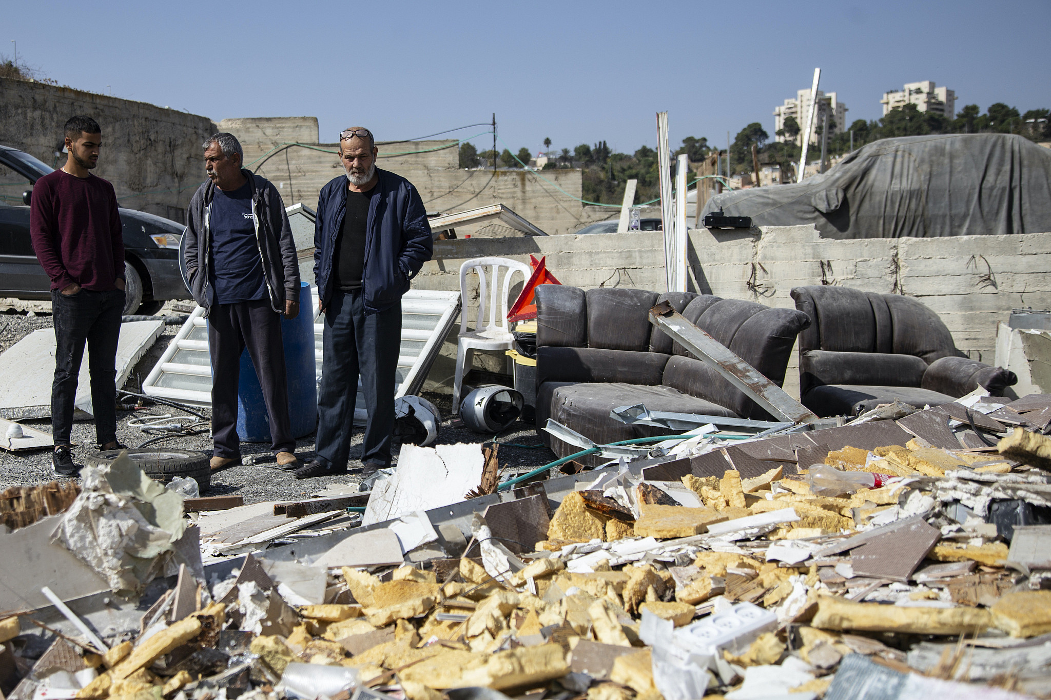 Ishaq Hamdan, center, stands by the remains of his home after it was demolished by Israeli authorities, Issawiya, East Jerusalem, November 7, 2019. (Faiz Abu Rmeleh/Activestills.org)