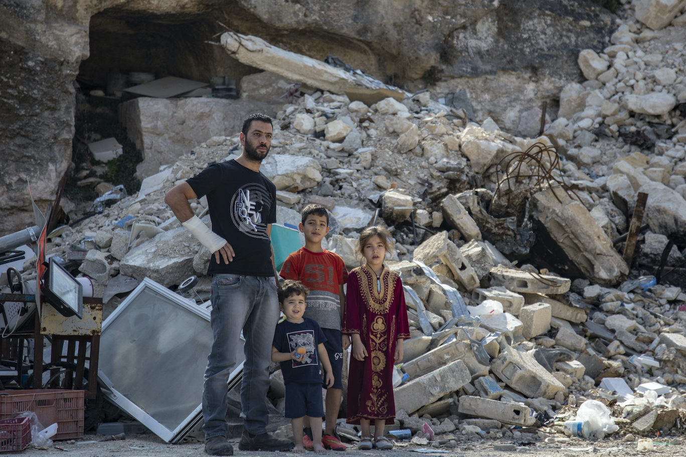 Quosay Burqan stands with his children in front of the ruins of their home in Silwan, East Jerusalem, after it was demolished by Israeli authorities, November 8, 2019. (Faiz Abu Rmeleh/Activestills.org)