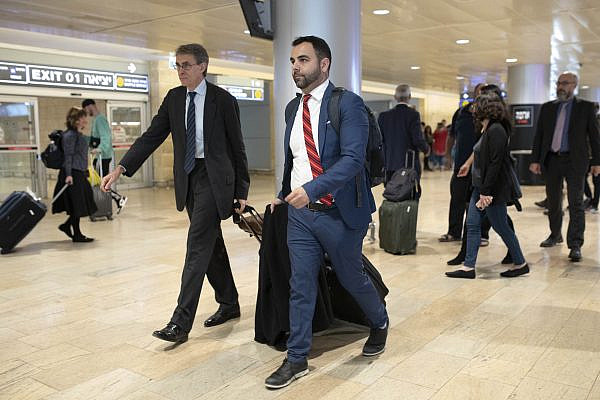 Human Rights Watch Israel and Palestine Director Omar Shakir walks through Ben-Gurion Airport, accompanied by HRW head Kenneth Roth, left, ahead of his deportation from Israel, November 25, 2019 (Oren Ziv/Activestills.org).