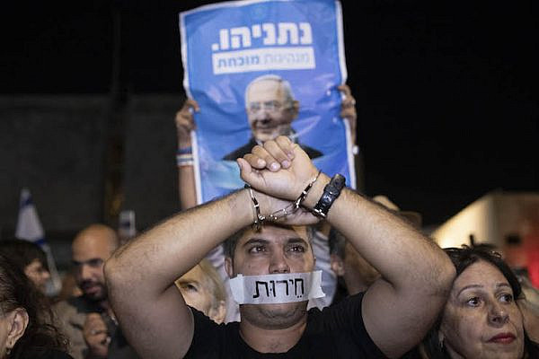 Thousands take part in a pro-Netanyahu rally outside the Tel Aviv Museum, less than a week after Israel's attorney general announced he would file bribery charges against the prime minister, November 26, 2019. (Oren Ziv)