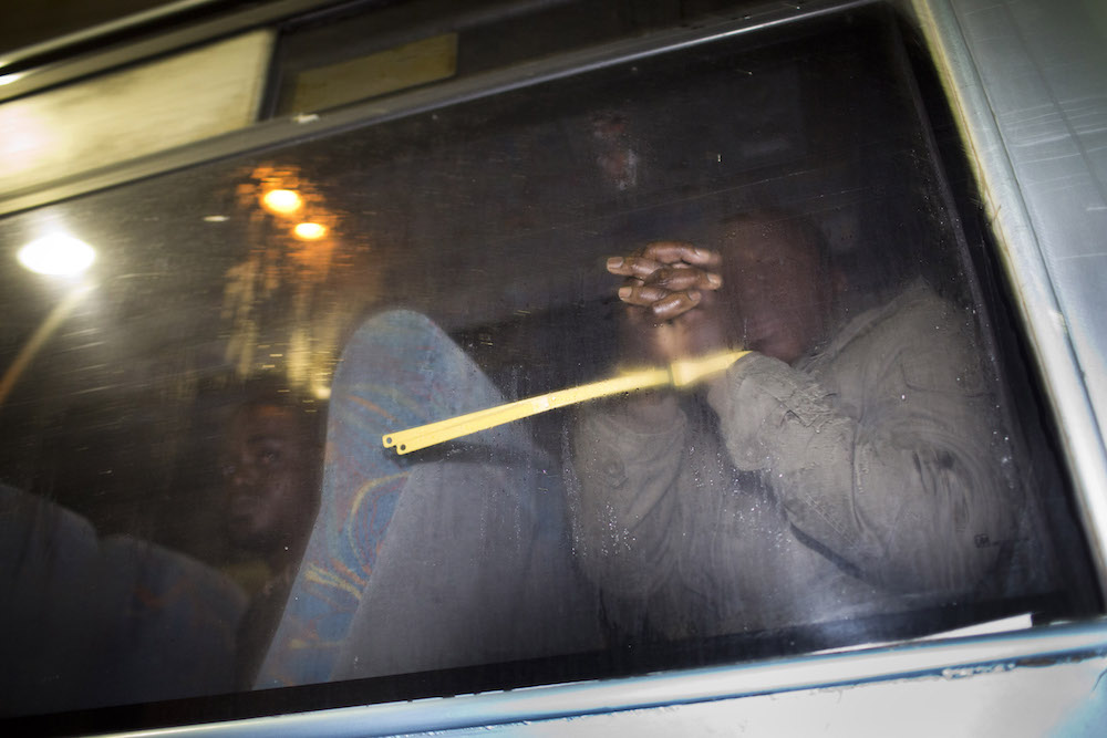 Handcuffed African refugees sit in a van after being arrested by immigration authorities in south Tel Aviv, Israel, December 22, 2012. (Oren Ziv/Activestills.org)