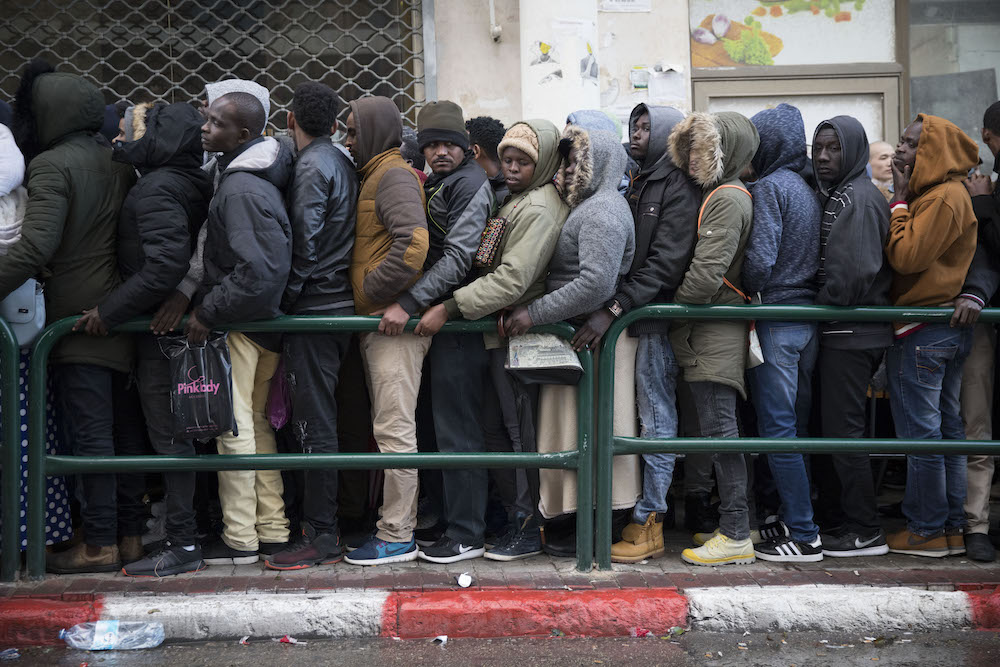 Asylum seekers line up to renew their visas outside an Interior Ministry office in South Tel Aviv in 2018. (Oren Ziv/Activestills.org)