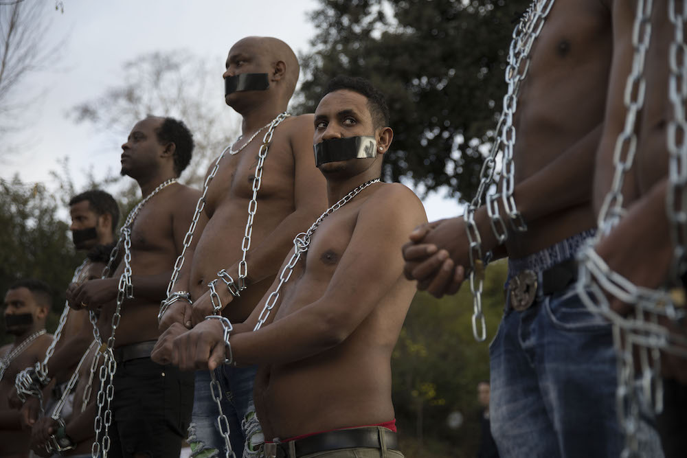 Asylum seekers from Sudan and Eritrea hold mock slave auctions outside the embassy of Rwanda in Herzliya, near Tel Aviv, during a protest against the Israeli government's plan to deport African asylum seekers to third countries in Africa, January 22, 2018. (Oren Ziv/Activestills.org)