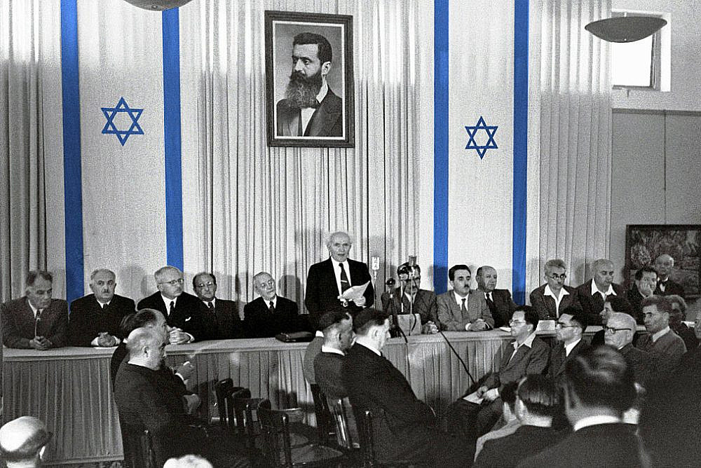 David Ben-Gurion publicly pronouncing the Declaration of the State of Israel, May 14 1948, beneath a large portrait of Theodor Herzl, founder of modern political Zionism, in the old Tel Aviv Museum of Art building on Rothschild St. (Rudi Weissenstein / Israel Ministry of Foreign Affairs)