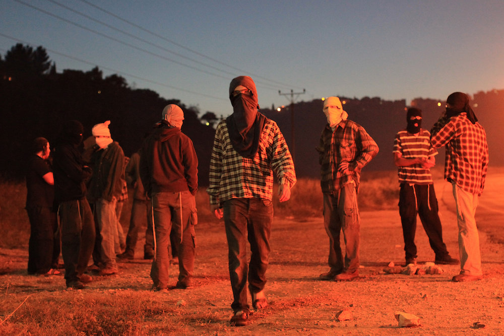 Illustrative photo of masked Jewish settlers in the West Bank. (Kobi Gideon/Flash90)