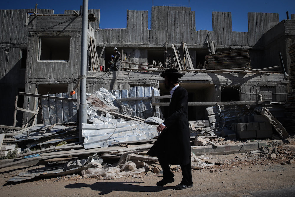 An ultra-Orthodox man walks by construction in the settlement of Beitar Illit, June 17, 2015. (Nati Shohat/Flash90)