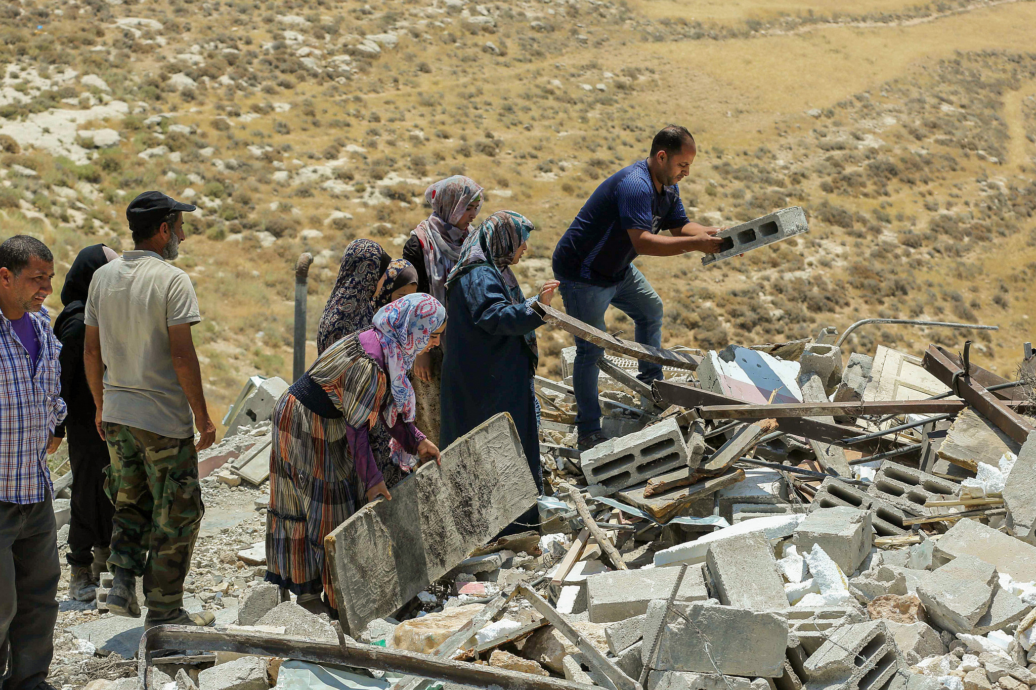 Palestinians pick through houses demolished by Israeli authorities in the West Bank village of Khalat Aldabe, south of Yatta, June 17, 2019. (Wissam Hashlamon/Flash90)