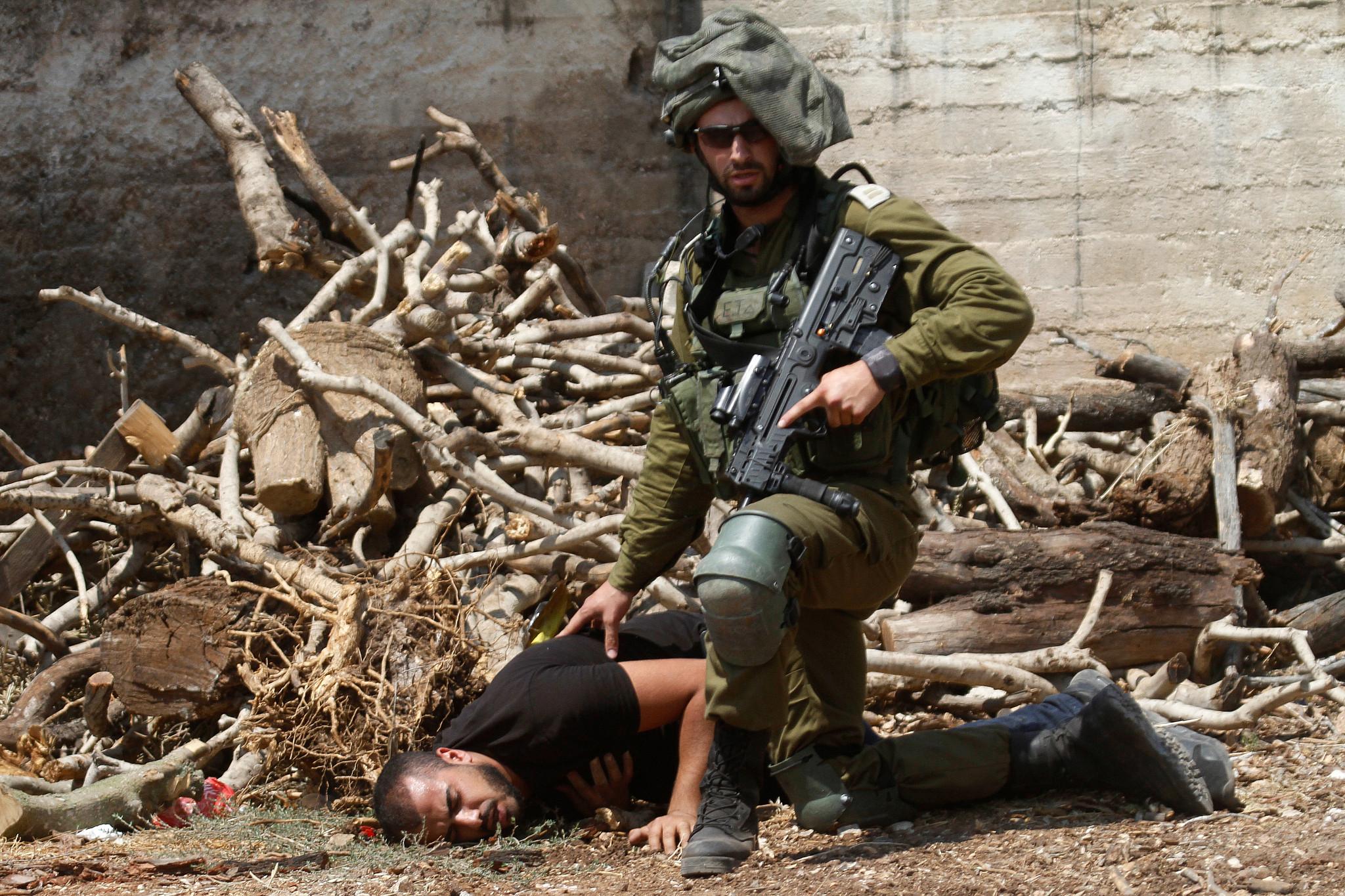 An Israeli soldier kneels over a Palestinian protester in the village of Kfar Qaddum, near Nablus, West Bank August 23, 2019. (Nasser Ishtayeh/Flash90)
