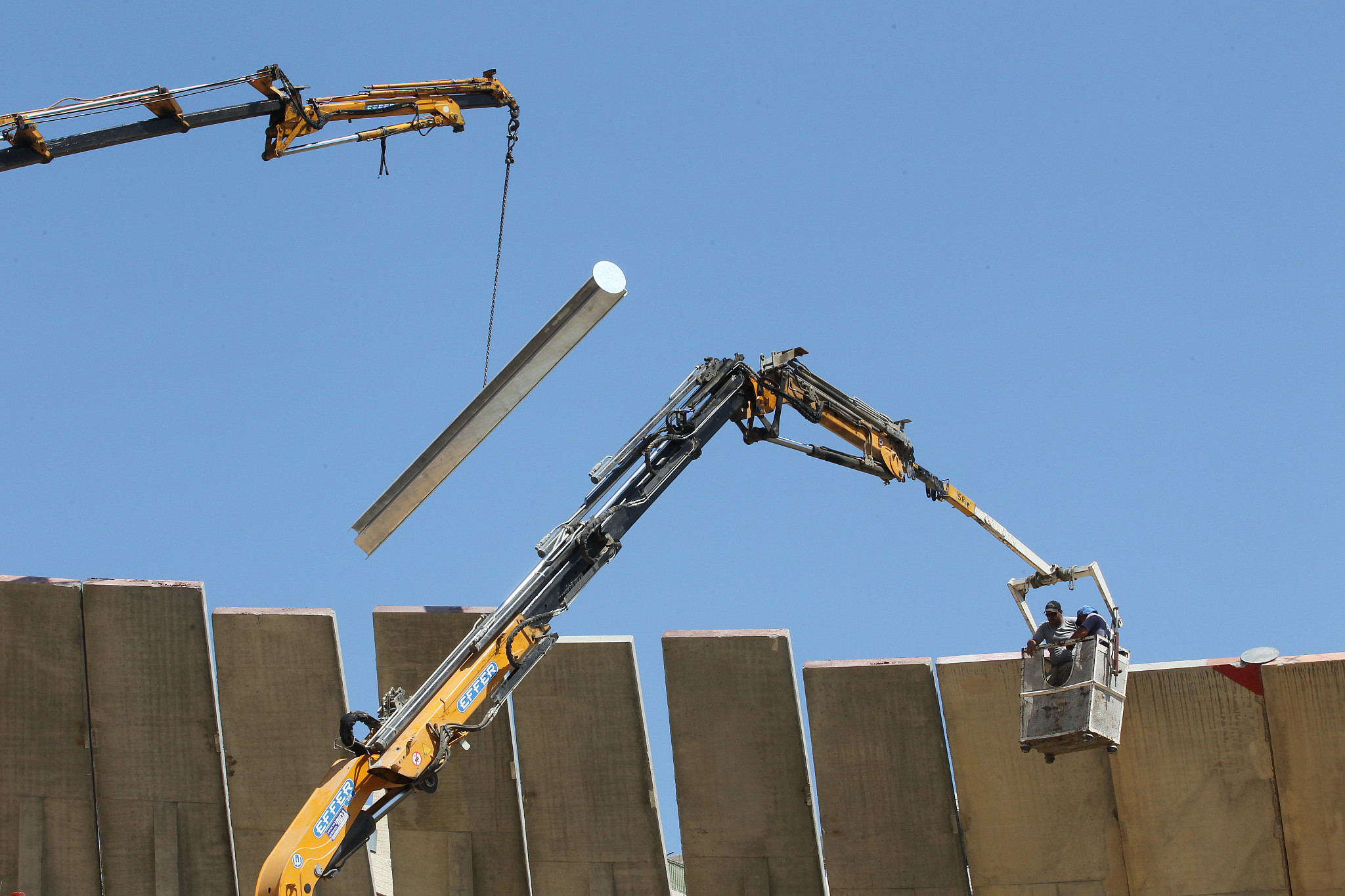 Palestinian construction workers work on part of the separation wall between the Gush Etzion settlement bloc and Jerusalem, July 7, 2011. (Nati Shohat/Flash90)