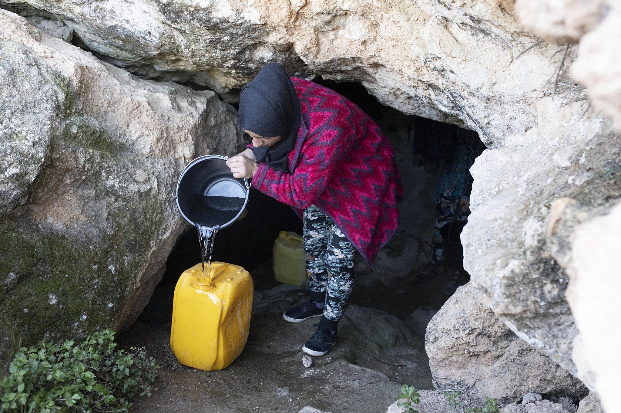 A Palestinian woman draws water from the newly-reclaimed Ein Albeida spring, South Hebron Hills, January 3, 2020. (Oren Ziv/Activestills.org)