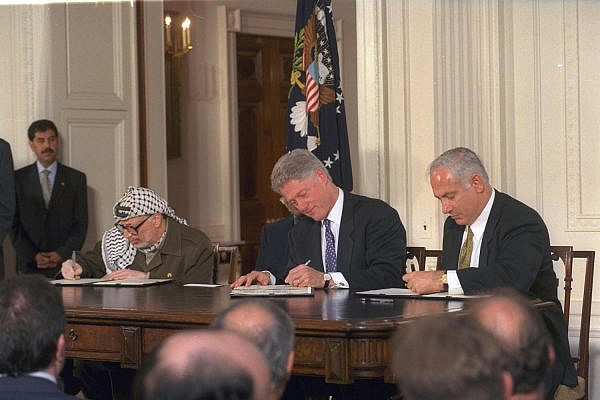 Israeli Prime Minister Benjamin Netanyahu, President, U.S. President Bill Clinton, and Palestinian Authority leader Yasser Arafat sign the Wye River Memorandum at the White House, October 23, 1998. (Avi Ohayon/GPO)