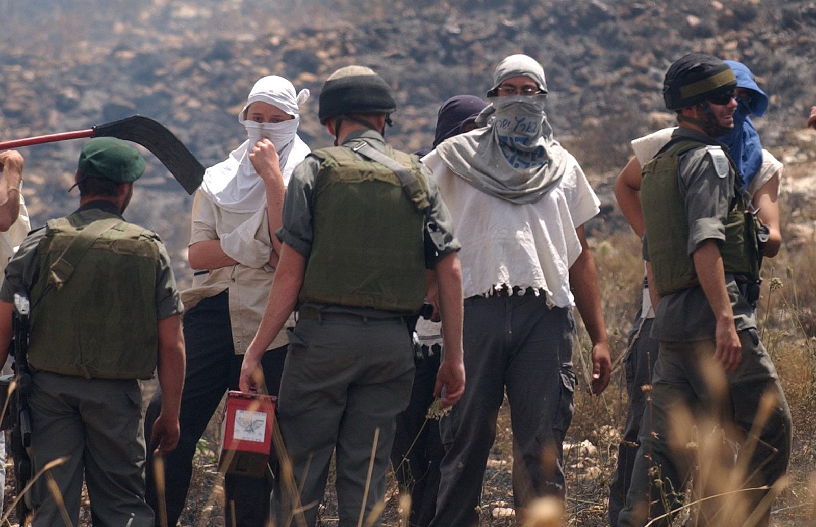 Masked Israeli settlers watch after Palestinian fields were set on fire in the village of Asira al-Qiblyia in the northern West Bank on June 2, 2010. According to Palestinian villagers, Jewish settlers from the nearby Yitzhar settlement set ablaze their olive and wheat fields. (Wagdi Ashtiyeh/Flash90)