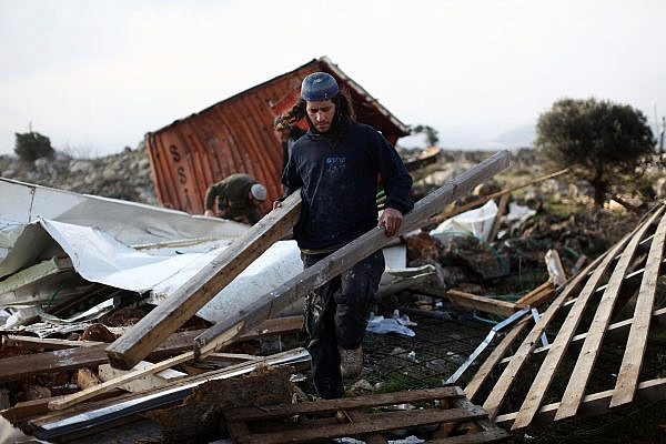 Jewish settler clears the rubble from structures demolished by the IDF in the unauthorized Jewish settlement outpost of Mitzpe Yitzhar, West Bank, on 15 December 2011. (Kobi Gideon / Flash90)