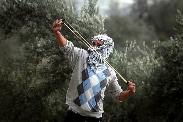 A Palestinian student from Birzeit University uses a slingshot to throw stones at Israeli troops during clashes with soldiers at the Atara checkpoint as they protest against Israel's military action on the Gaza Strip. November 19, 2012. (Issam Rimawi / FLASH90)