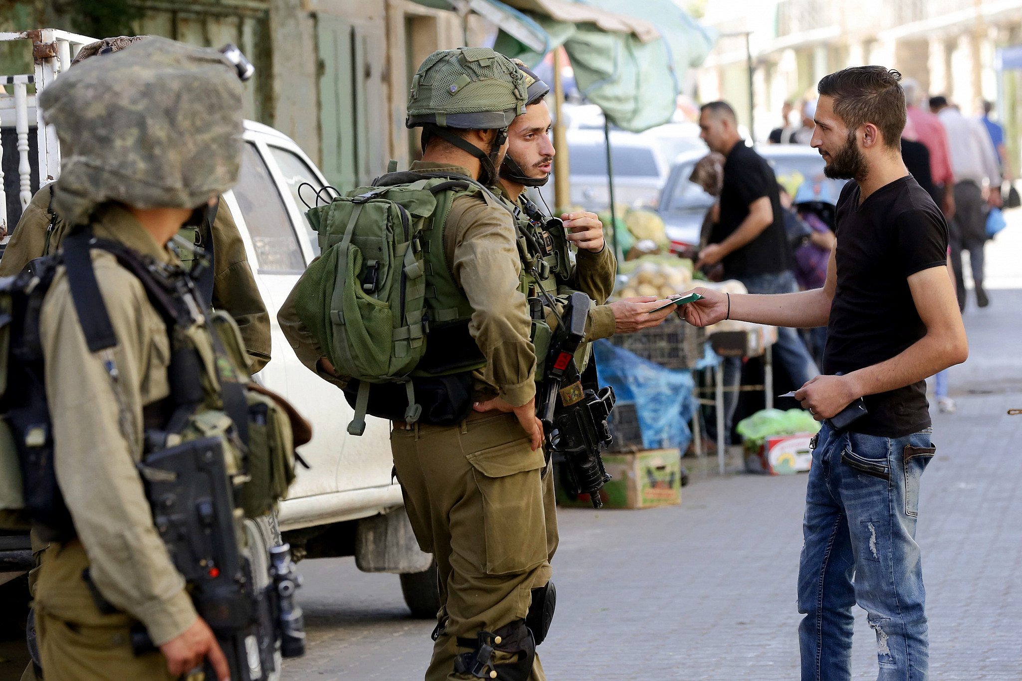 An Israeli soldier checks the ID of a Palestinian man in the West Bank city of Hebron, June 19, 2017. (Wisam Hashlamoun/Flash90)