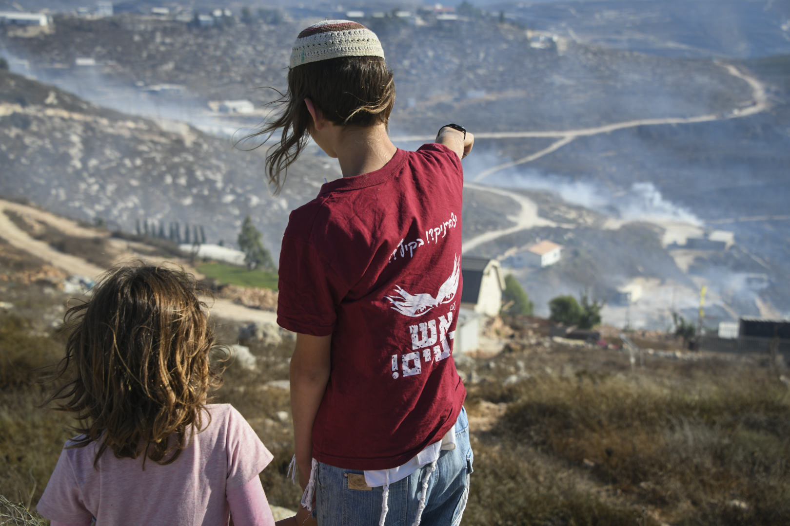Jewish children look at a forest fire raging in Yitzhar, in the West Bank, on August 15, 2019. (Sraya Diamant/Flash90)