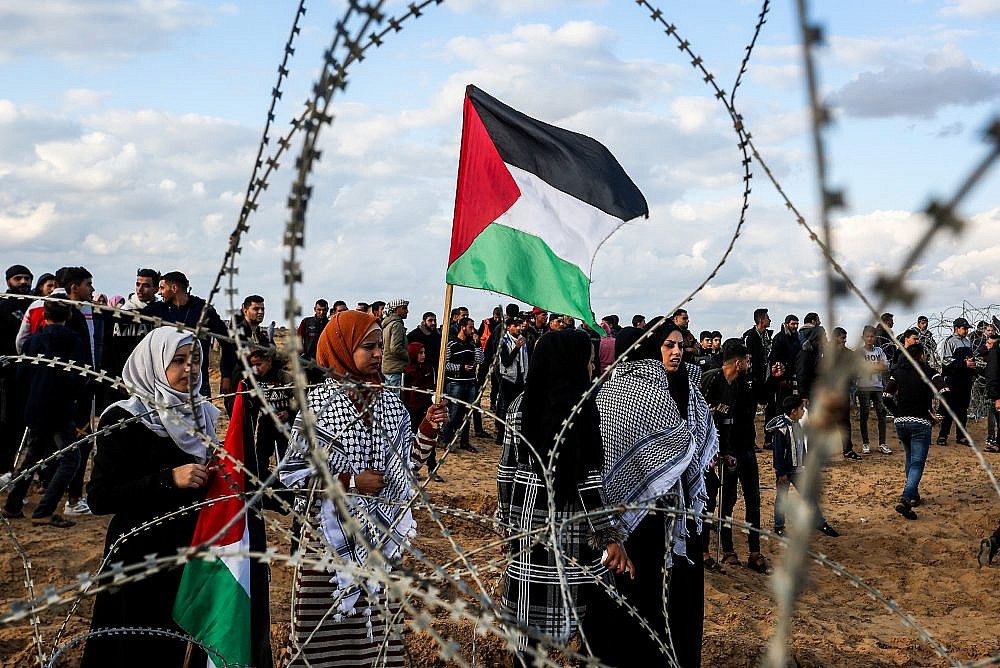 Palestinian demonstrators stand alongside the Gaza border fence during a protest, east of Rafah in the southern Gaza Strip, December 6, 2019. (Abed Rahim Khatib/Flash90)
