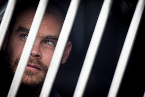 Israeli activist Jonathan Pollak seen in the Magistrate's Court in Jerusalem, arrested as part of an unprecedented private suit by Ad Kan, January 7, 2020. (Yonatan Sindel/Flash90)