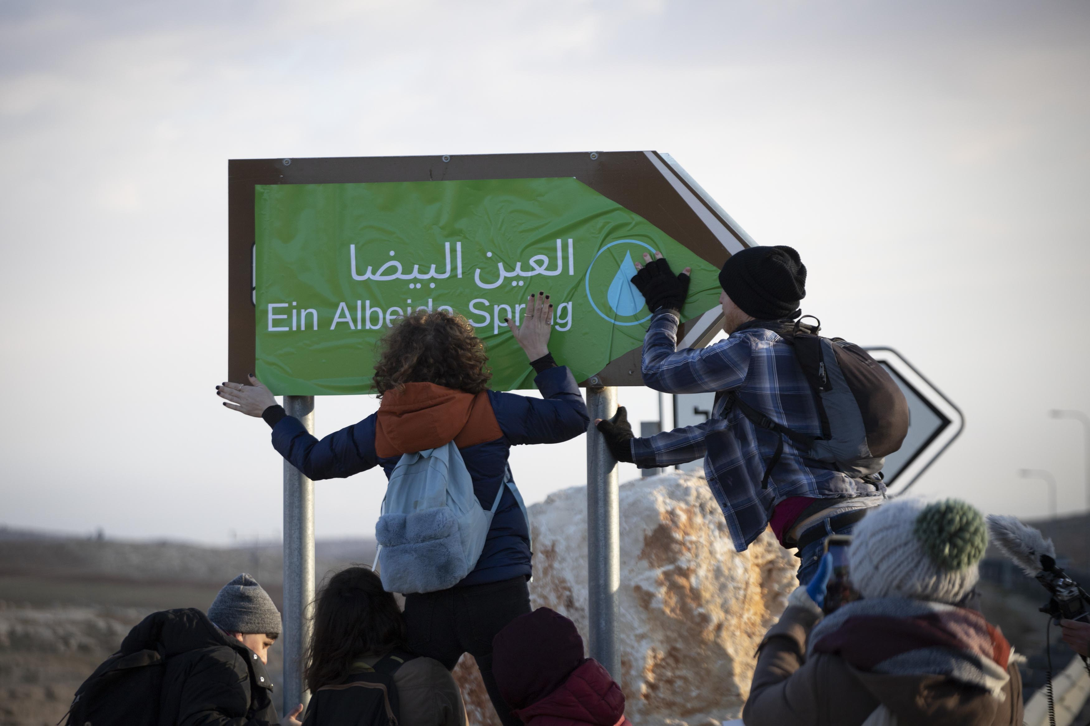 Activists affix a new sign pointing to Ein Albeida spring along Route 60, South Hebron Hills, January 3, 2020. (Oren Ziv/Activestills.org)