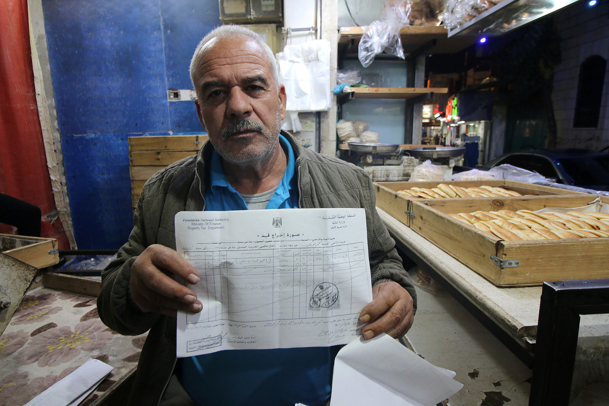 Ahmad Qaddoura holds a Palestinian Authority-issued registration document of his land, December 22, 2019. (Ahmad Al-Bazz)