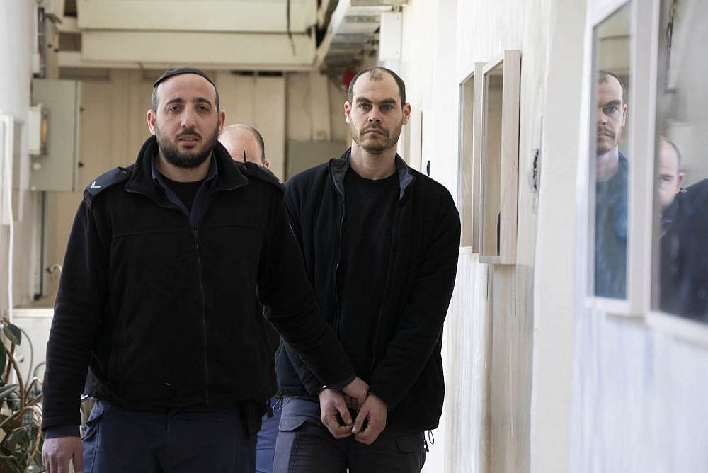Israeli left-wing activist Jonathan Pollak is led to the Jerusalem Magistrate's Court for a hearing, January 30, 2020. (Oren Ziv)
