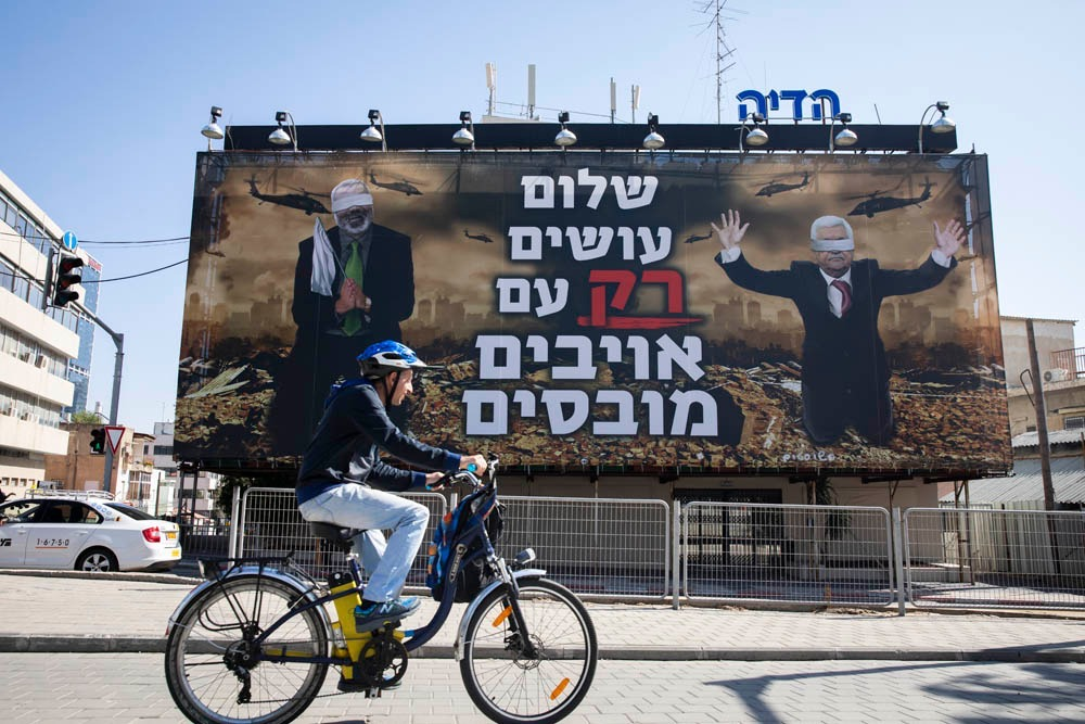 A billboard put up by the far-right Israel Victory Project in Tel Aviv shows blindfolded Palestinian leaders Ismail Haniyeh and Mahmoud Abbas. The caption reads: 'Peace is made with defeated enemies.' (Oren Ziv)