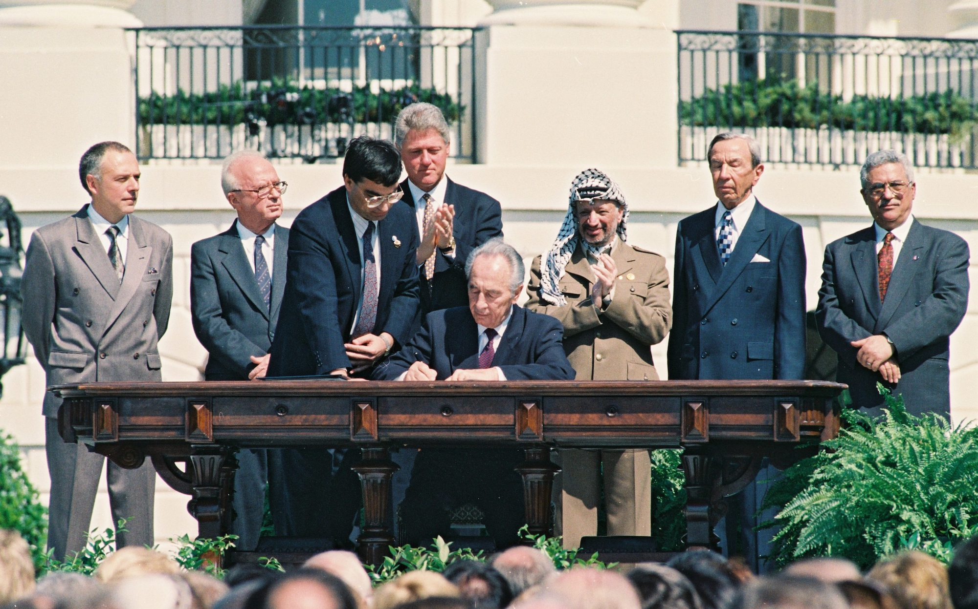 Israeli Foreign Minister Shimon Peres signs the Oslo Accords on the White House Lawn. Behind him are U.S. President Bill Clinton, PLO Chairman Yasser Arafat, Israeli Prime Minister Yitzhak Rabin, Palestinian Prime Minister Mahmoud Abbas and other world leaders, Washington DC, September 13, 1994. (Avi Ohayon/GPO)