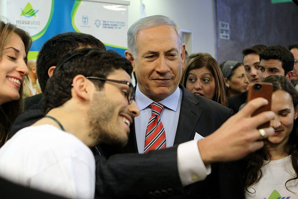 """Prime Minister Benjamin Netanyahu seen taking a """"selfie"""" with students before the start of the weekly cabinet meeting at the Prime Minister's Office in Jerusalem on March 30, 2014. (Danny Meron/POOL/Flash90)"""