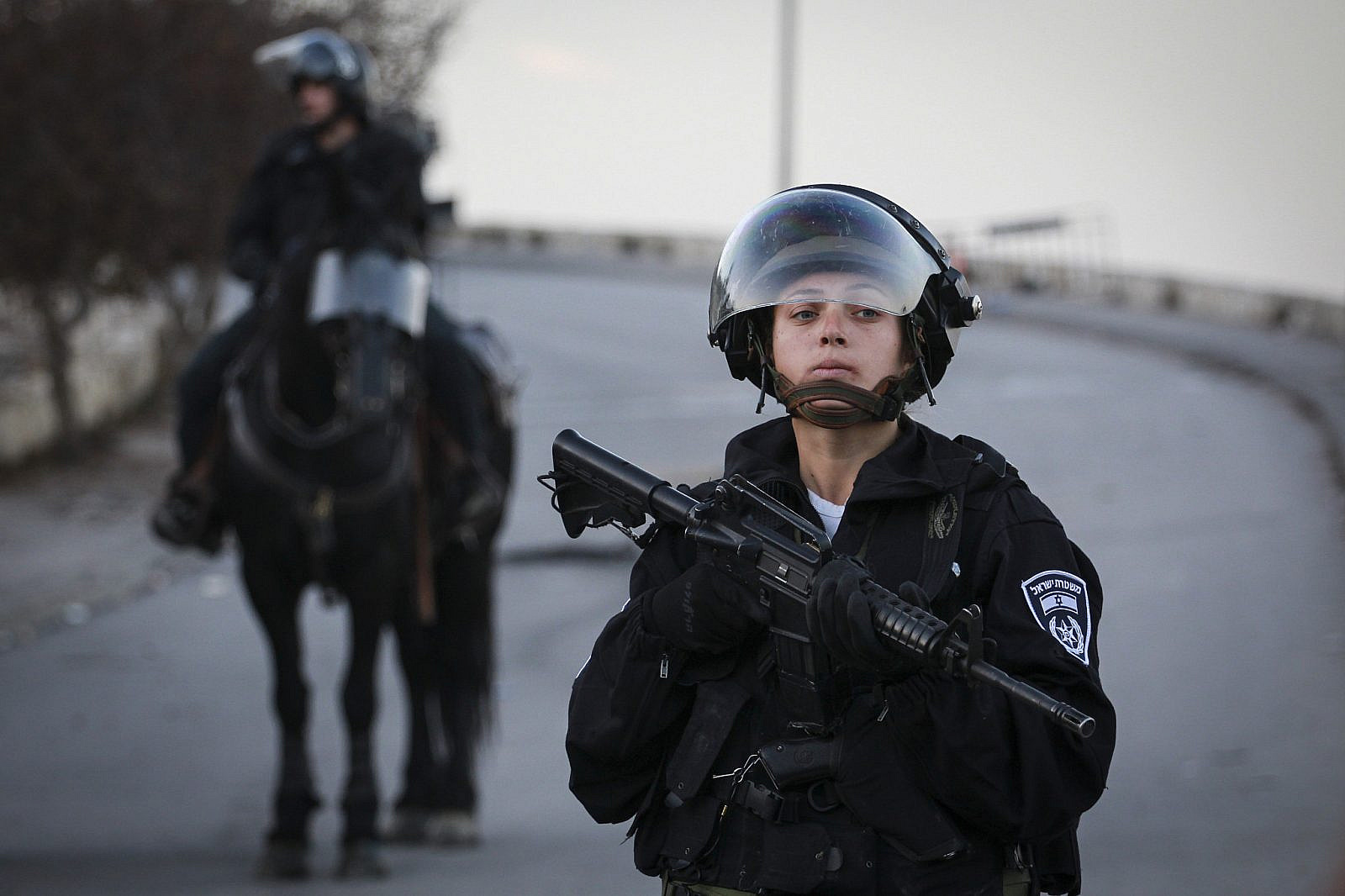 An Israeli Border Policewoman stands guard during a demonstration in Issawiya, East Jerusalem, against the new cement blockades at the entrances to Issawiya, on November 12, 2014. (Hadas Parush/Flash90)