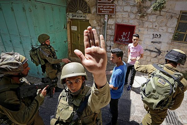 Illustrative photo of an Israeli soldier attempting to block the view of a photographer as soldiers search Palestinian men in the West Bank city of Hebron, on June 22, 2017. (Wisam Hashlamoun/Flash90)