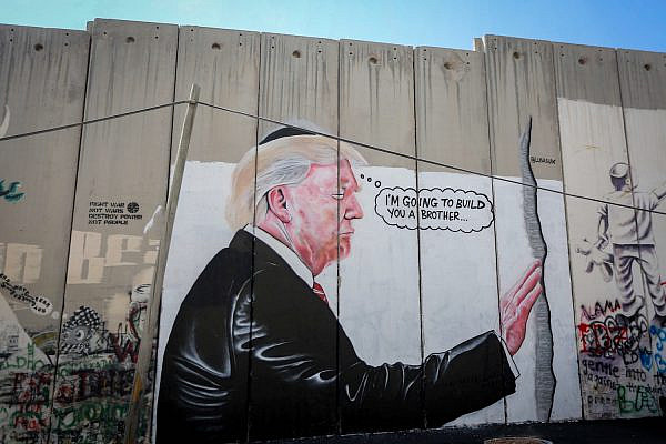 A mural depicting President Donald Trump kissing an Israeli army watchtower on the separation wall in the West Bank city of Bethlehem, August 4, 2017. (Flash90)