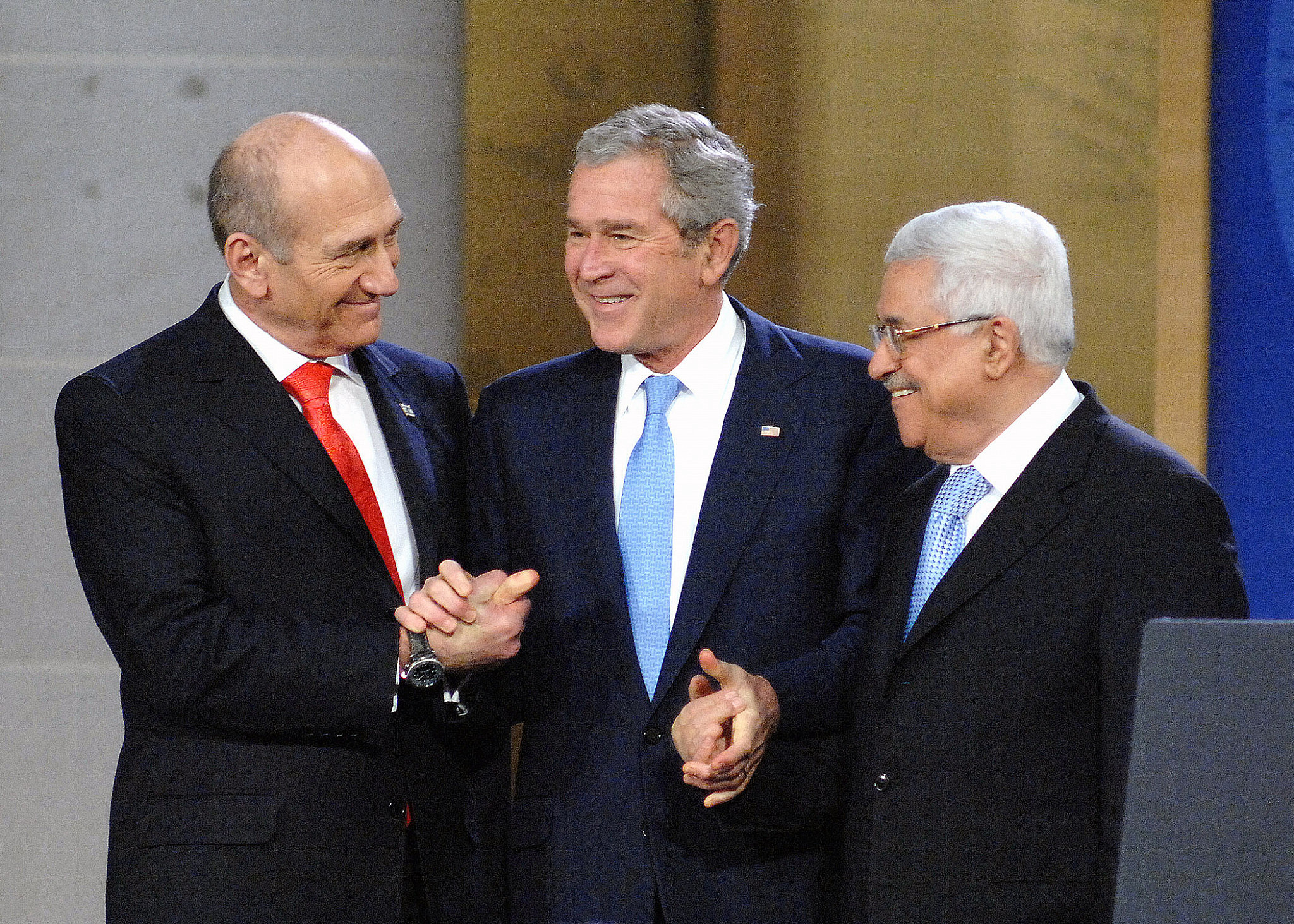 Israeli Prime Minister Ehud Olmert, President George W. Bush, and Palestinian President Mahmoud Abbas shake hands at the Annapolis Conference in the Naval Academy's Memorial Hall in Annapolis, Maryland, November 27, 2007.(Gin Kai/U.S. Navy)