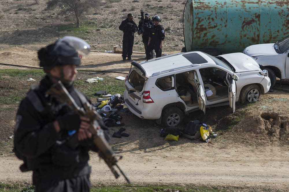 Israeli police officer seen by the vehicle belonging to Yacoub Abu Al-Qi'an, who was shot and killed by officers during a raid on the Bedouin village of Umm al-Hiran on January 17, 2017. (Activestills.org)